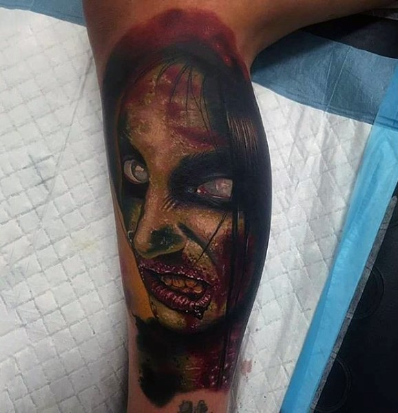 Horror movie style multicolored leg tattoo of zombie woman face