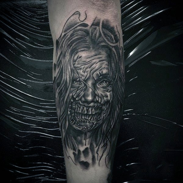 Horror style black and white forearm tattoo of creepy monster woman