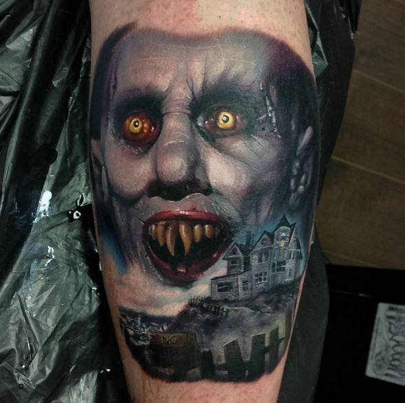 Horror style colored arm tattoo of vampire face with old house