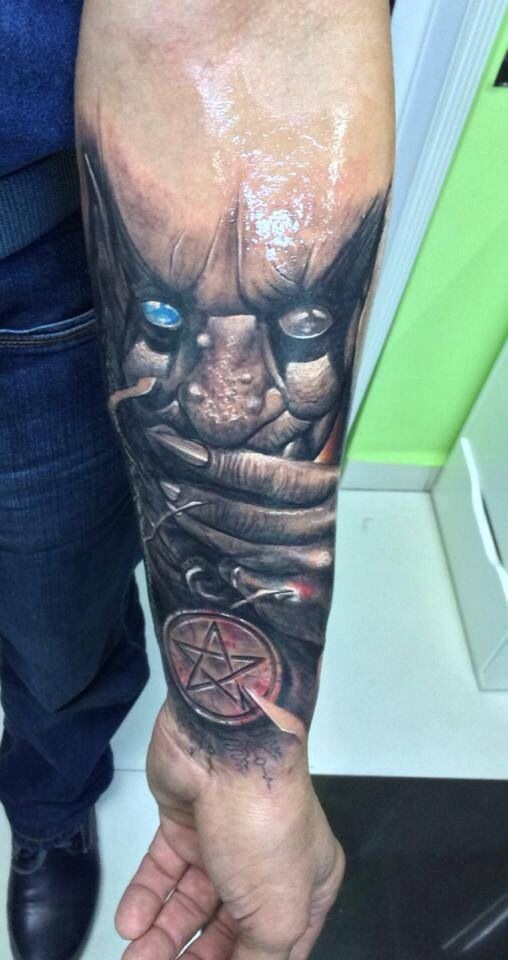 Horror style colored forearm tattoo of monster with blue eye