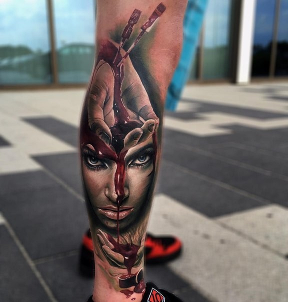 Horror style colored leg tattoo of bloody arm with woman face