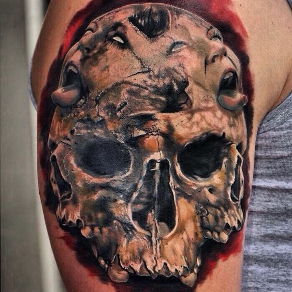 Horror style colored shoulder tattoo of human skull with monster faces