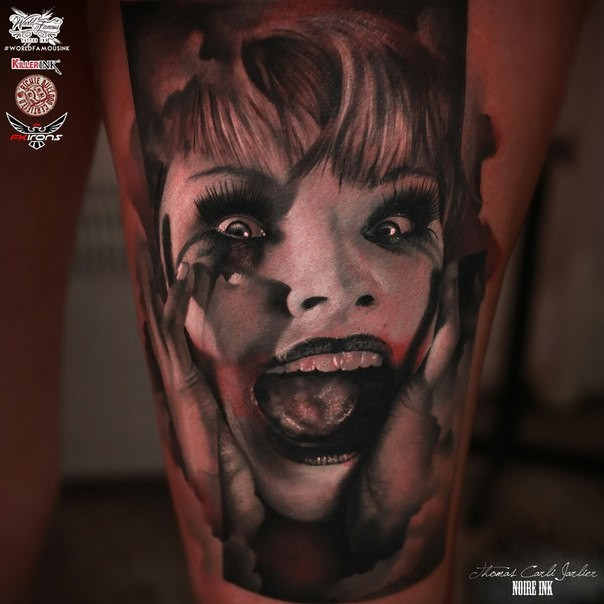 Horror style colored thigh tattoo of creepy screaming woman