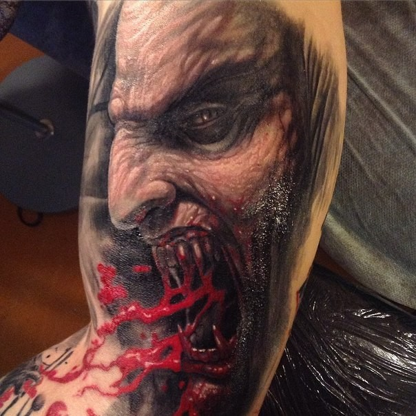 Horror style creepy looking biceps tattoo of bloody vampire