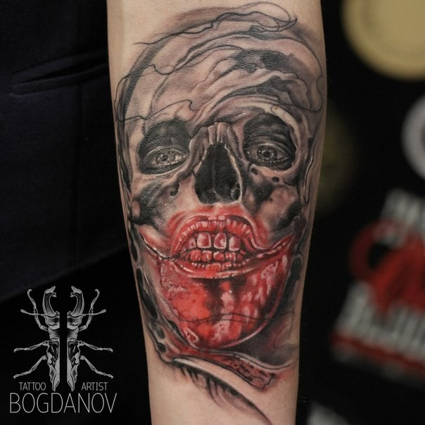Horror style creepy looking forearm tattoo of bloody monster face