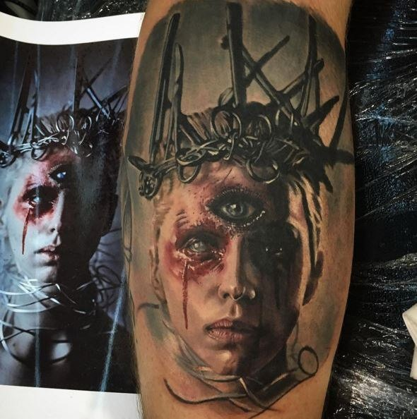Horror style creepy looking leg tattoo of mysterious monster face with vine