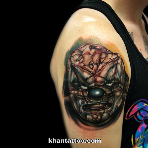 Horror style creepy looking shoulder tattoo of demonic clown face