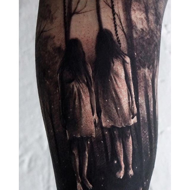 Horror style creepy looking sisters in forest tattoo on arm