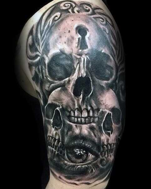 Horror style creepy looking upper arm tattoo of skulls with keyhole