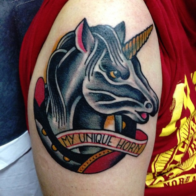 Horseshoe and unicorn portrait colored shoulder tattoo with funny banner lettering in old school style