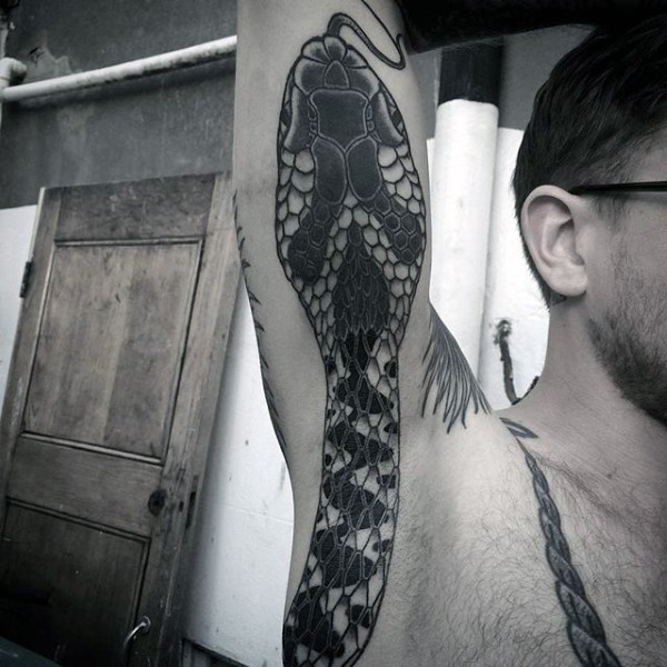 Huge detailed snake tattoo on man&quots arm and side in traditional old style
