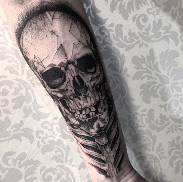 Human skull and skeleton tattoo on forearm in engraving style