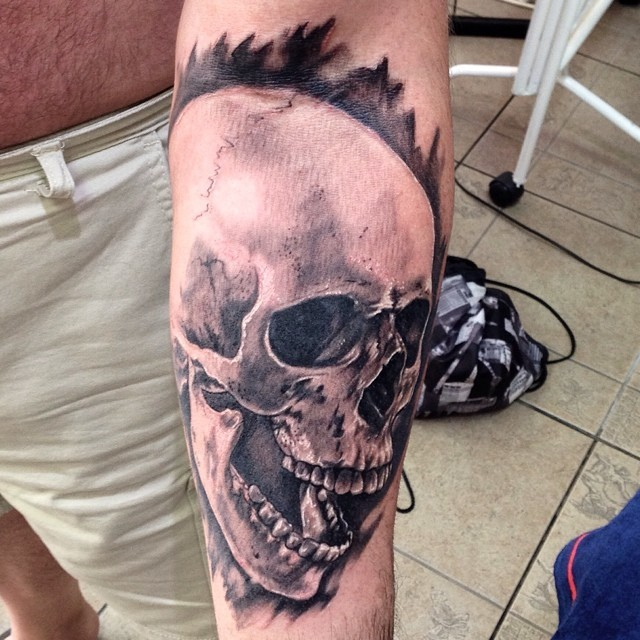 Human skull with open jaw black and white realistic forearm tattoo with dark haze