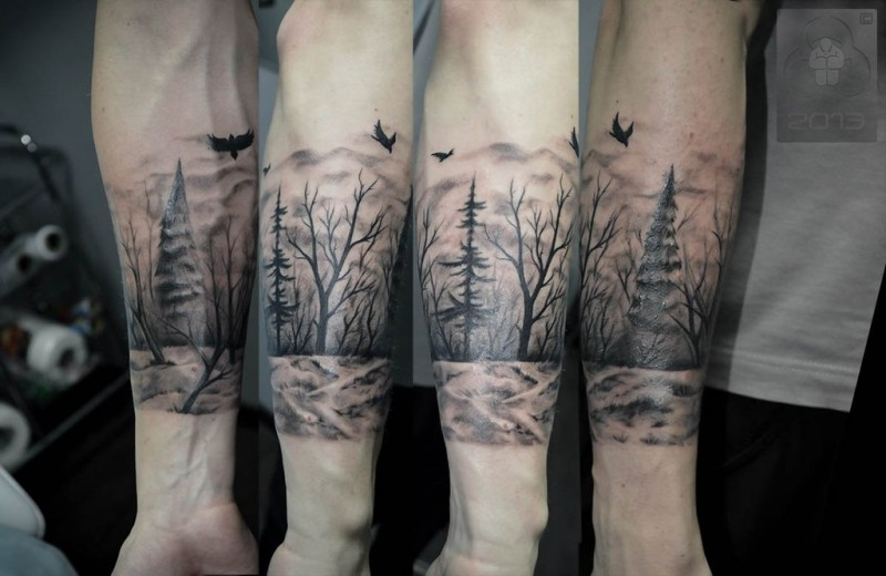 Illustrative style black and white forearm tattoo of dark forest and crows