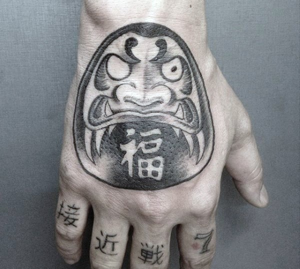 Illustrative style black and white hand tattoo of daruma doll with lettering