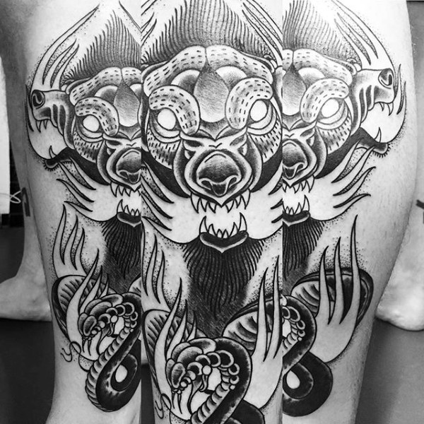 Illustrative style black and white leg tattoo of Cerberus with flames and snake