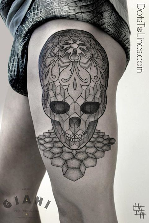 Illustrative style black ink thigh tattoo of alien skull stylized with ornaments