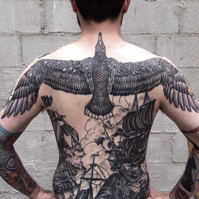 Illustrative style black ink whole back tattoo of large bird with ships