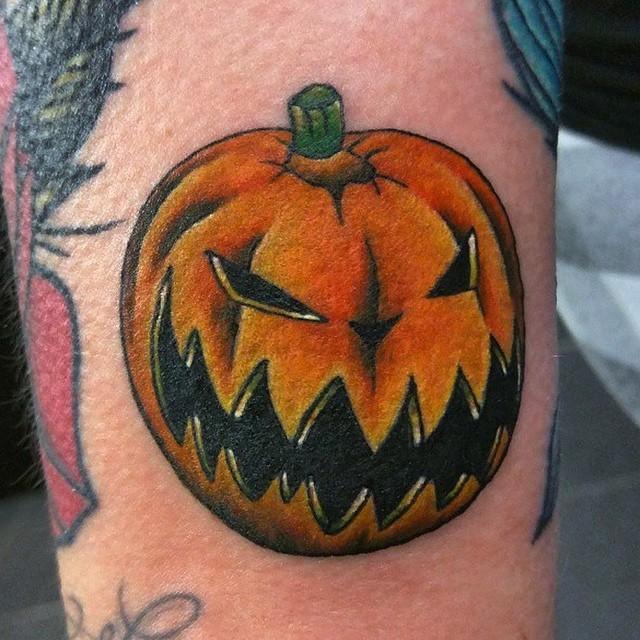 Illustrative style colored arm tattoo of evil pumpkin