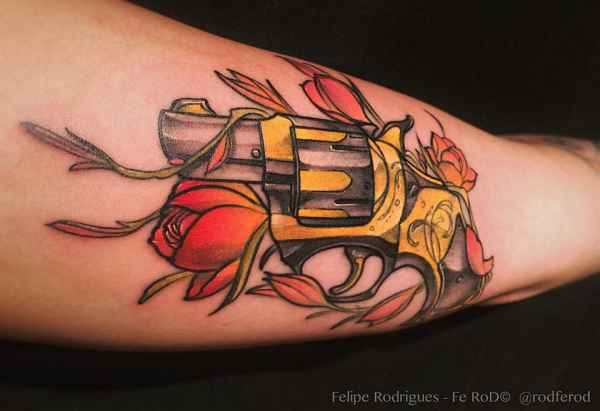 Illustrative style colored arm tattoo of small pistol with flowers
