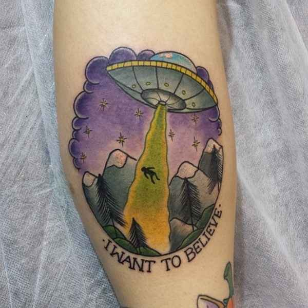 Illustrative style colored arm tattoo of alien ship stealing human with lettering