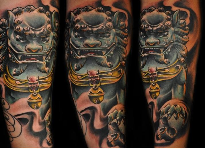 Illustrative style colored arm tattoo of ancient mask and human skull