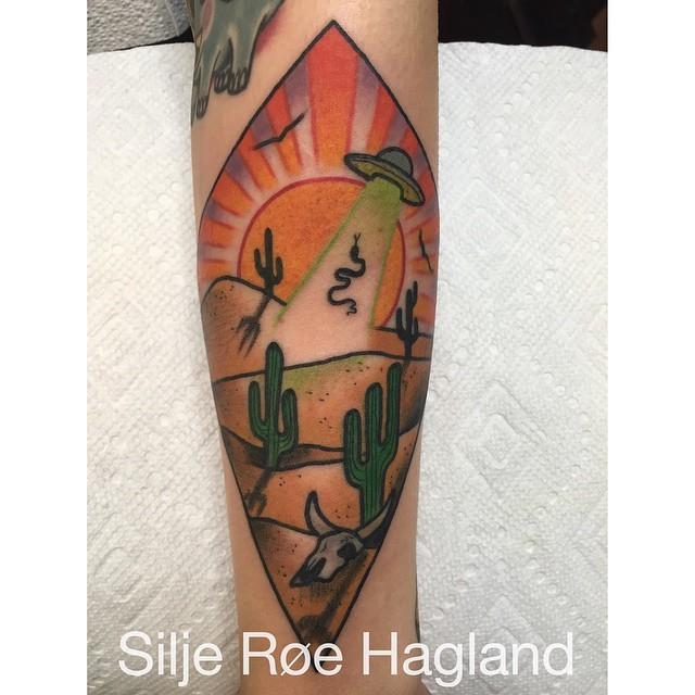 Illustrative style colored arm tattoo of desert with alien ship