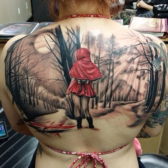 Illustrative style colored back tattoo of little girl in dark forest