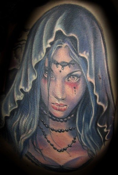 Illustrative style colored demonic woman in hood tattoo