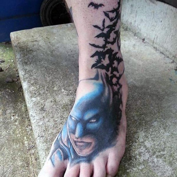 Illustrative style colored foot tattoo of Batman with butterflies