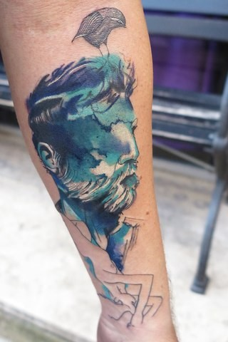 Illustrative style colored forearm tattoo of man with beard and bird
