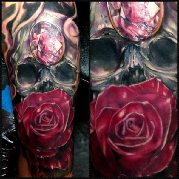 Illustrative style colored forearm tattoo of human skull with jewelry and rose