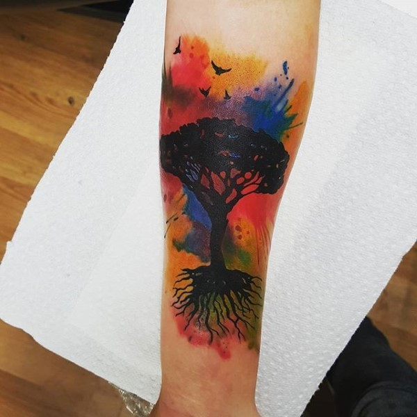 Illustrative style colored forearm tattoo of tree with birds