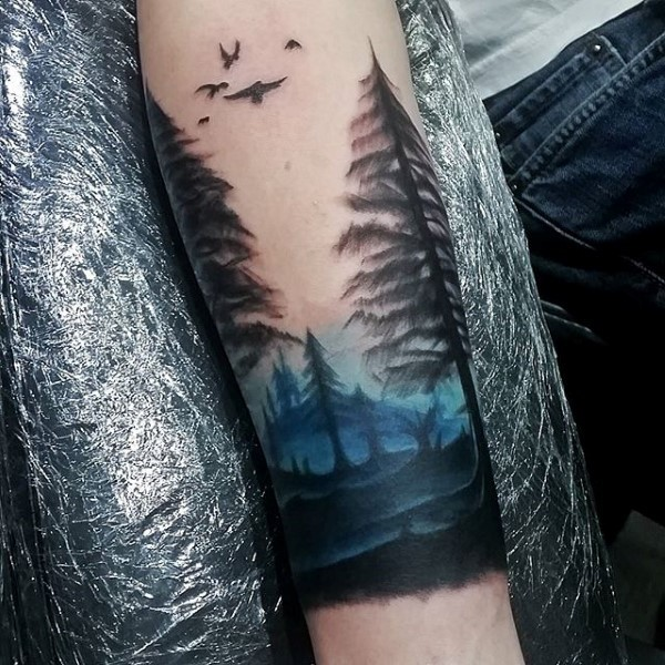 Illustrative style colored forearm tattoo of natural forest with birds