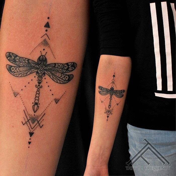 Illustrative style colored forearm tattoo of dragonfly with ornaments