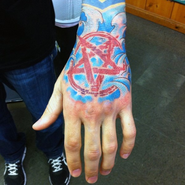 Illustrative style colored hand tattoo of red demonic star