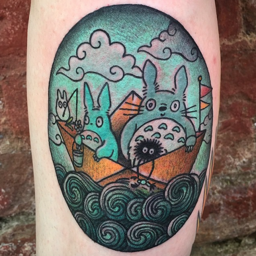 Illustrative style colored leg tattoo of funny cartoon monsters in paper ship