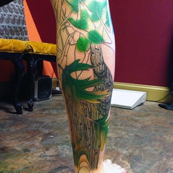 Illustrative style colored leg tattoo of trees with mountains