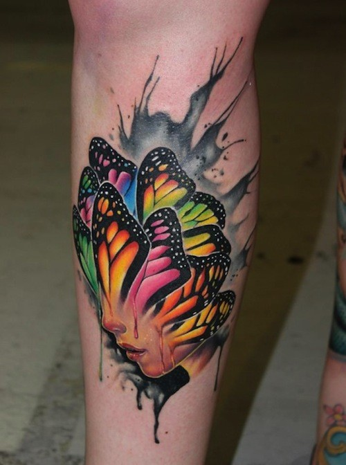 Illustrative style colored leg tattoo of human face stylized with butterfly wings
