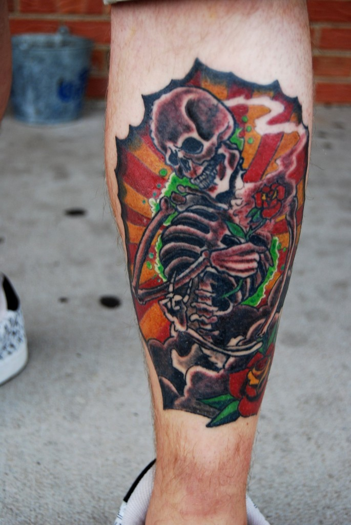 Illustrative style colored leg tattoo of human skeleton and rose