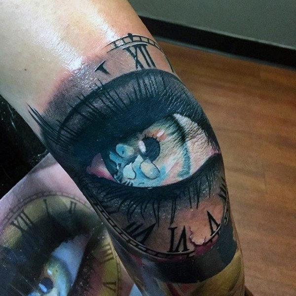 Illustrative style colored leg tattoo of woman eye with clock
