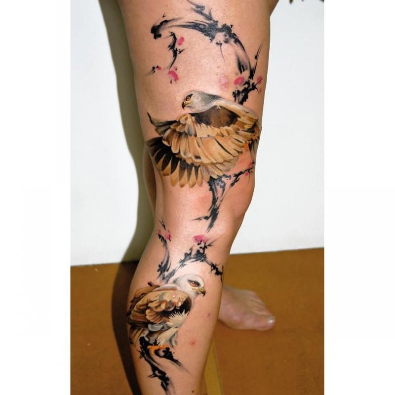 Illustrative style colored leg tattoo of beautiful eagles