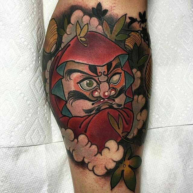 Illustrative style colored leg tattoo of big daruma doll with flowers