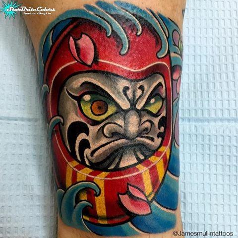 Illustrative style colored leg tattoo of daruma doll with wave