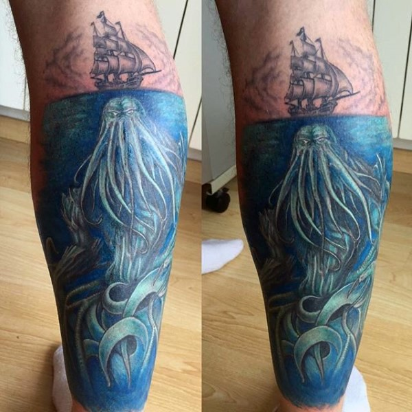 Illustrative style colored leg tattoo of small ship with large underwater monster