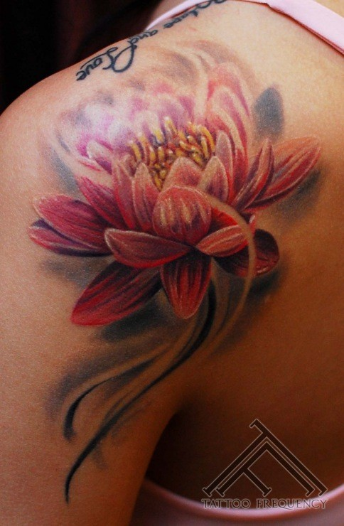 Illustrative style colored lotus flower tattoo on shoulder
