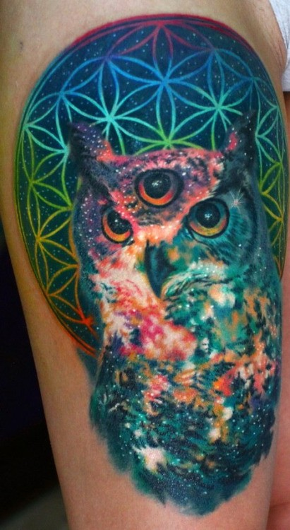 Illustrative style colored mystical owl tattoo on thigh with unusual symbol