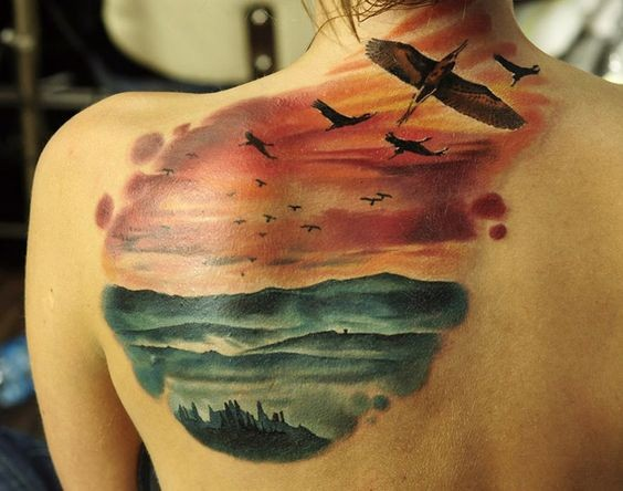 Illustrative style colored scapular tattoo of flying birds and ocean