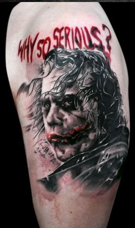 Illustrative style colored shoulder tattoo of Joker face and lettering