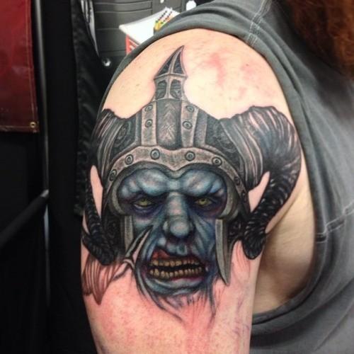 Illustrative style colored shoulder tattoo of demonic warrior head